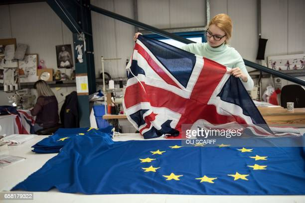 A flag manufacturer folds finished Union Flags and EU flags at the factory of 'Flagmakers' in Chesterfield northern England on March 24 2017 The...