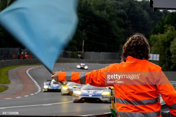 Flag marshal waves a blue flag to oncoming cars during morning warm-uo before the 24 Hours of Le Mans on June 18 2016 in Le Mans France.