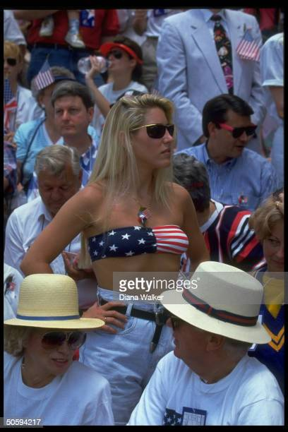 Flag motif bikini braclad young woman standing out amid patriotic spectators at Desert Storm gulf war victory parade