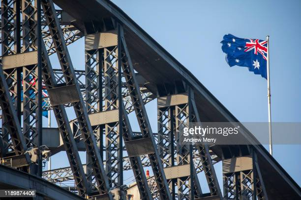 flag of australia, australian flag on top of the sydney harbour bridge with blue sky - australian flag stock pictures, royalty-free photos & images