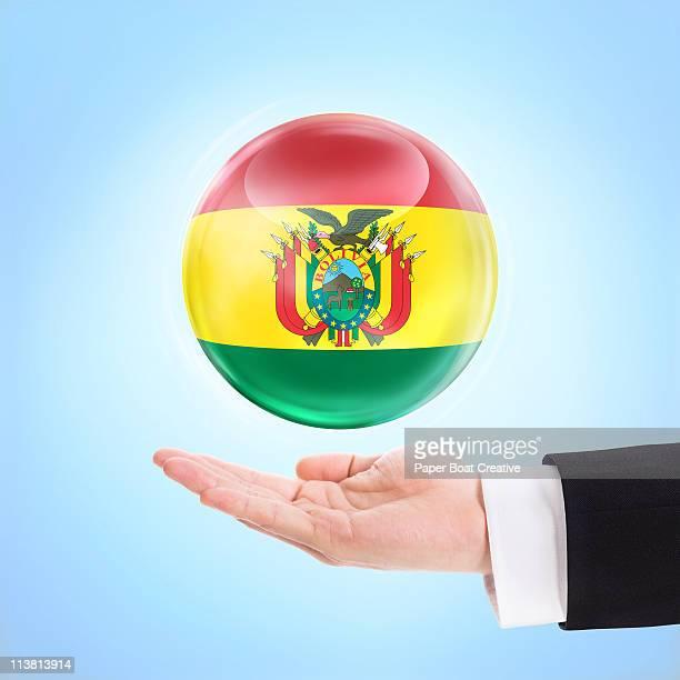 flag of bolivia being supported by a hand - bandera boliviana fotografías e imágenes de stock
