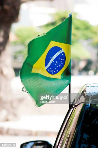 Flag of Brazil waving off a cars door window