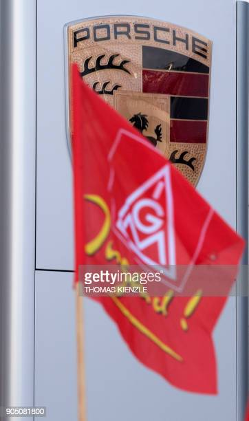 A flag of German metalworkers' union IG Metall waves in front of the Porsche logo during a warning strike of employees of German car maker Porsche in...