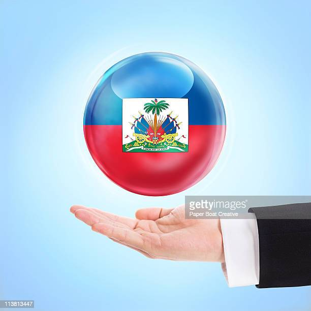 flag of haiti being supported by a hand - haitian flag stock pictures, royalty-free photos & images