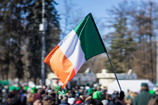 Flag of Ireland close-up in hands on background of blue sky during the celebration of St. Patrick's Day 1083318012