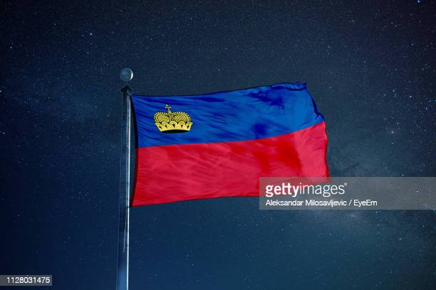 flag of liechtenstein against star field sky - liechtenstein stock pictures, royalty-free photos & images