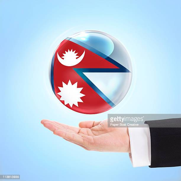 flag of nepal being supported by a hand - nepali flag stock pictures, royalty-free photos & images