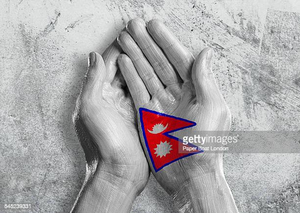 flag of nepal painted on two hands together - nepali flag stock pictures, royalty-free photos & images