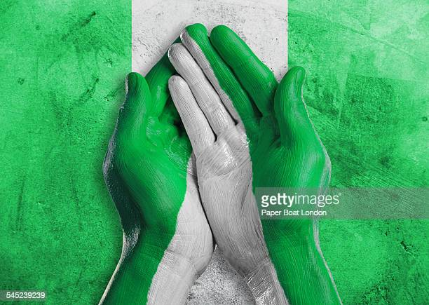 flag of nigeria painted on two hands together - nigerian flag stock photos and pictures