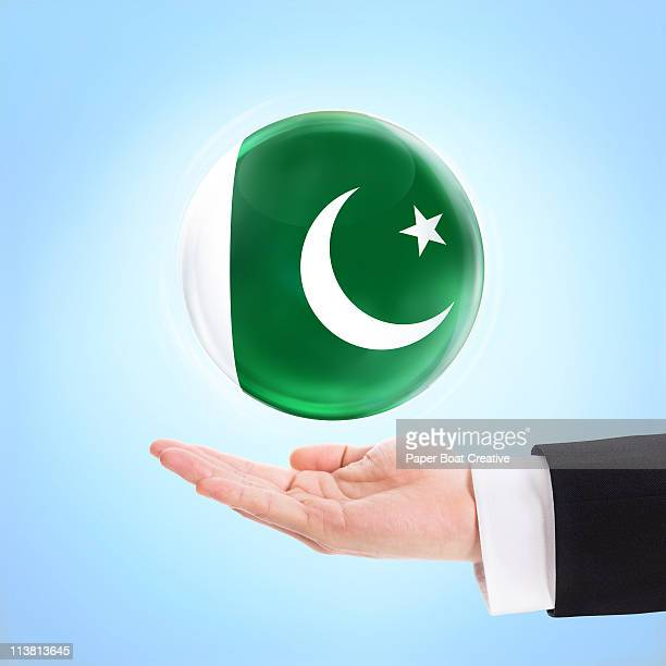 flag of pakistan  being supported by a hand - pakistani flag stock photos and pictures