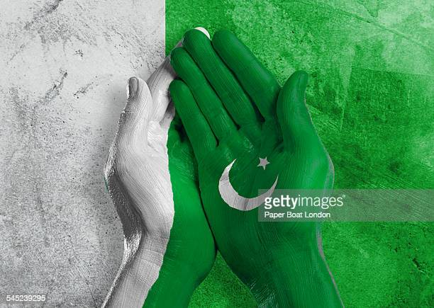 flag of pakistan painted on two hands together - pakistani flag stock photos and pictures