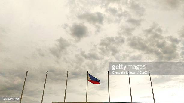flag of philippine against cloudy sky - philippines flag stock pictures, royalty-free photos & images