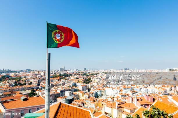 flag of portugal waving in the wind against clear blue sky, lisbon, portugal - bandeira de portugal imagens e fotografias de stock