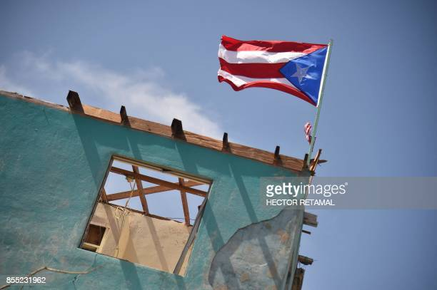 A flag of Puerto Rico is seen on a damaged house in Yabucoa in the east of Puerto Rico on September 28 2017 The US island territory working without...