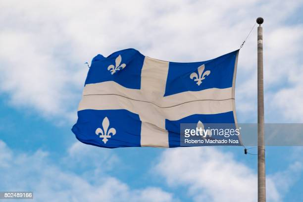 Flag of Quebec province flying waving in the air in clear sky day