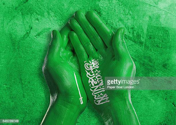 flag of saudi arabia painted on two hands - saudi arabian flag stock photos and pictures