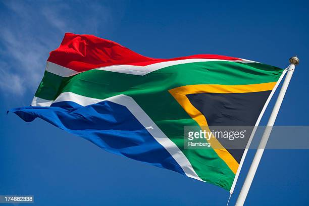 flag of south africa blowing in wind against blue sky - south african flag stock photos and pictures