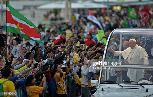 A flag of Suriname flutters as Pope Francis waves at faithfuls standing on the beachfront as he arrives on the popemobile at Copacabana beach to...