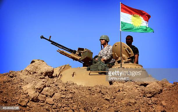 A flag of the autonomous Kurdistan region flies next to Iraqi Kurdish Peshmerga fighters standing on a tank as they hold a position on the front line...