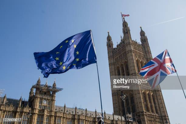 Flag of the European Union , left, flies with a Union flag, also known as a Union Jack, near the Houses of Parliament in London, U.K., on Monday,...