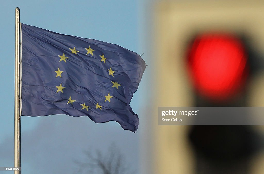 A flag of the European Union waves in the wind near a traffic light showing red on November 30, 2011 in Berlin, Germany. Many European leaders are warning that the growing debt crisis within the Eurozone is reaching critical proportions and that only weeks remain to take decisive action if the Euro is to survive.