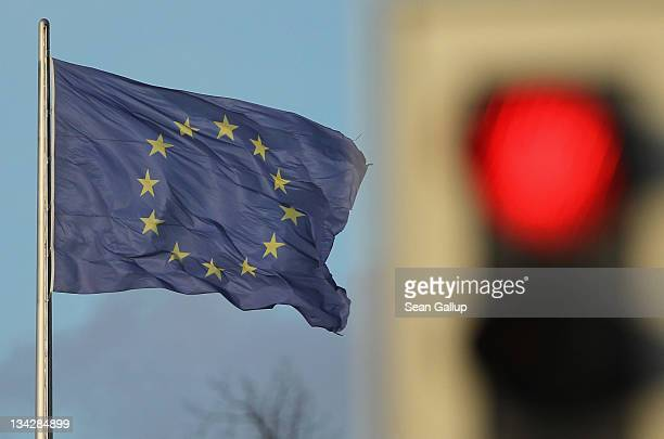 Flag of the European Union waves in the wind near a traffic light showing red on November 30, 2011 in Berlin, Germany. Many European leaders are...