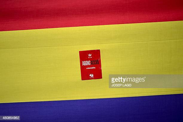 A flag of the Second Spanish Republic with stickers on it reading 'Abdication' is wrapped around the base of the monument on Juan Carlos square in...