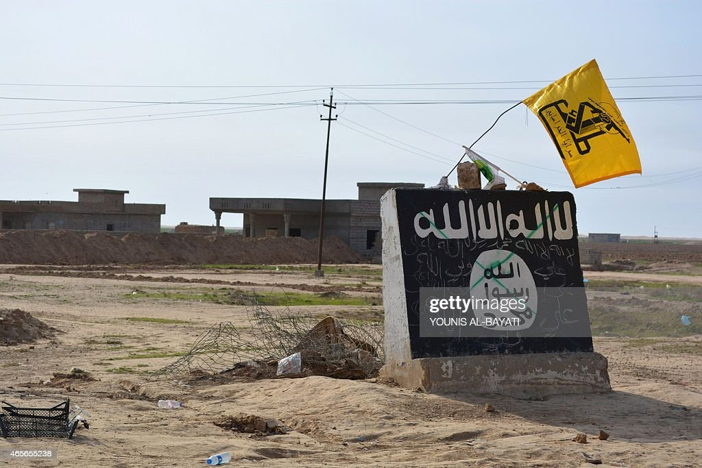 A flag of the Shiite Hezbollah militant group flutters over a mural depicting the emblem of the Islamic State (IS) group in Al-Alam village, northeast of the multi-ethnic Iraqi city of Tikrit, on March 9, 2015, during a military operation by Iraqi government forces and tribal fighters to regain control of the Tikrit region from jihadists. After being forced out of the province of Diyala earlier this year, the IS jihadists are now fighting off a huge assault on the city of Tikrit as government and allied forces continue to work their way north towards the main IS stronghold of Mosul.