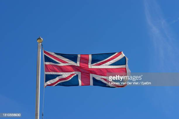 flag of the united kingdom union jack waving in a blue sky - insignia stock pictures, royalty-free photos & images