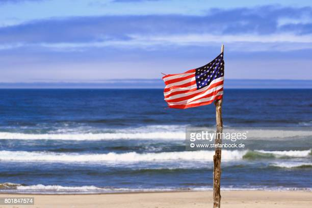 flag of the united states of america at rockaway beach, oregon - american flag ocean stock pictures, royalty-free photos & images