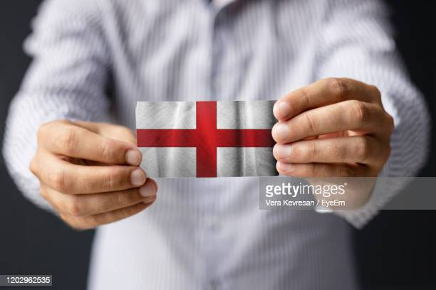 flag of united kingdom. close-up of man holding flag of england. - diplomacy stock pictures, royalty-free photos & images