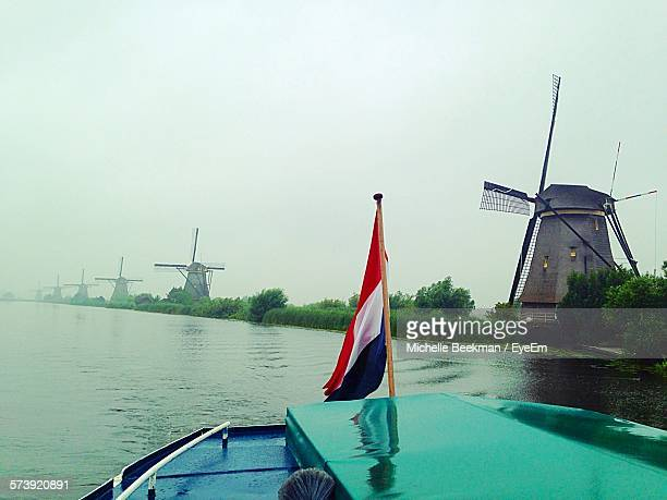 Flag On Cropped Boat Over River By Windmill Against Clear Sky