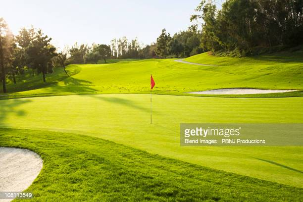 flag on golf course surrounded by sand traps - golf flag stock photos and pictures