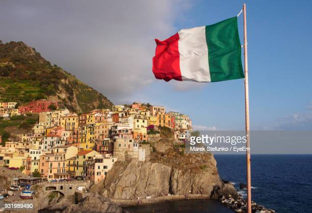 flag on mountain by sea against sky - marek stefunko stock pictures, royalty-free photos & images
