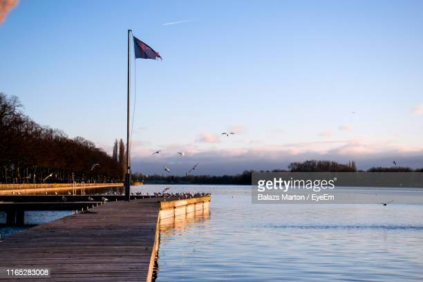 flag on pier over lake against sky during sunset - flagpole stock pictures, royalty-free photos & images