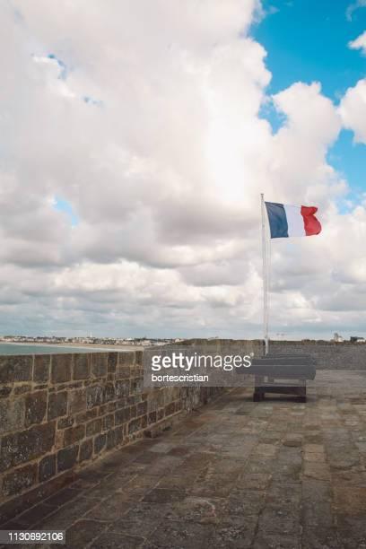 Flag On Promenade Against Cloudy Sky