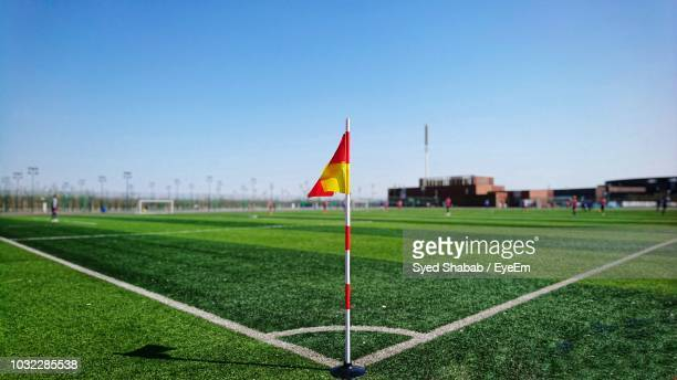 flag on soccer field against clear sky - football bulge stock photos and pictures