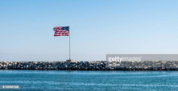 us flag on stone wall, los angeles, california, usa - american flag ocean stock pictures, royalty-free photos & images