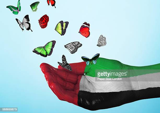 UAE flag painted on hand with butterflies