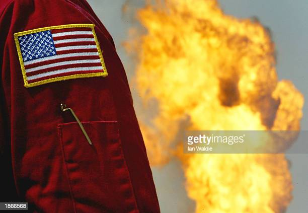 S flag patch is seen on the sleeve of a worker from Boots and Coots International Well Control at a burning oil well at the Rumayla oil fields March...