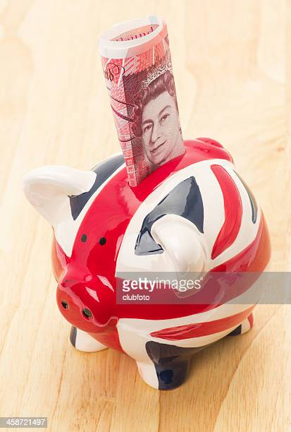 uk flag piggy bank with banknote - fifty pound note stock photos and pictures