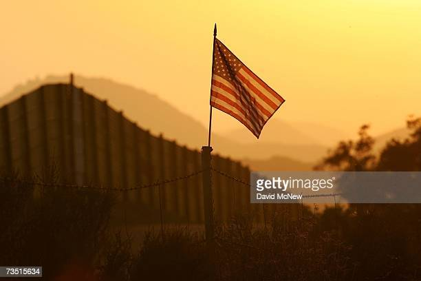 Flag put up by activists who oppose illegal immigration flies near the US-Mexico border fence in an area where they search for border crossers...