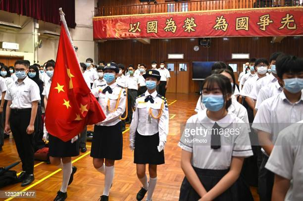 Flag raising team from the school marches in with a Flag of China, during a flag raising ceremony on the National Security Education Day, in a...