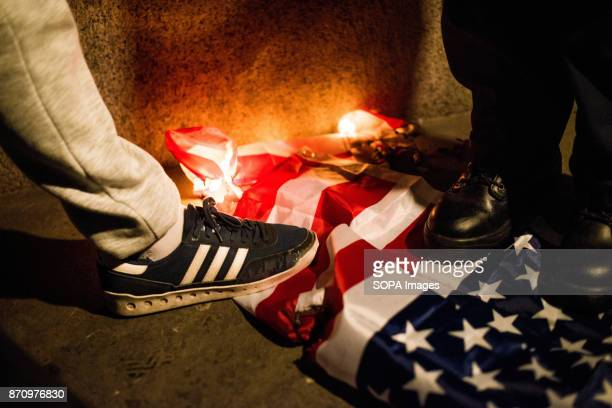 A flag seen stepped by a protester as it being set on fire during the March Demonstrators attend the Annual Million Mask March bonfire night protest...