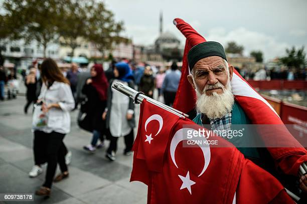 TOPSHOT A flag seller sells Turkish national flags near Istanbul's New Mosque in Eminonu on September 22 2016 / AFP / OZAN KOSE