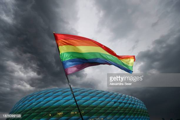Flag showing rainbow colours is pictured in front of the Allianz Arena soccer stadium illuminated in blue and green ahead of the Euro 2020 Group F...