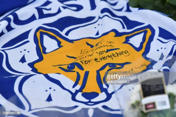 A flag showing the Leicester City Football Club's Fox logo with a message of thanks is seen in a growing pile of tributes outside Leicester City...