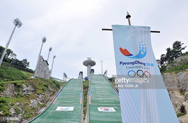 A flag showing the slogan and logo of Pyeochang's bid for the 2018 Winter Olympics stands at the ski jump stadium in the mountain resort of...