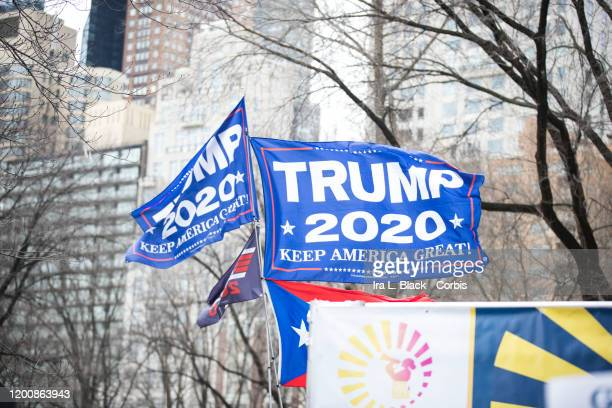 """Flag showing """"TRUMP 2020 Keep America Great """"waves over the stage of the Women's March in Central Park West during the Woman's March in the borough..."""