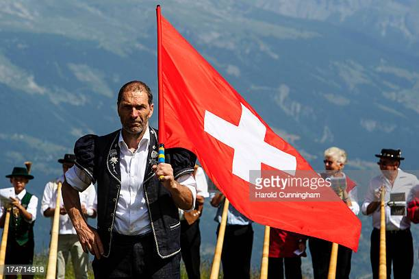 A flag thrower looks on as alphorn players prepare to perform on July 28 2013 in Nendaz Switzerland About 150 alphorn blowers performed together on...